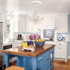 Don't feel obligated to use the same finishes on the island as you use on the cabinets. Here, a bright blue paint and copper countertop highlights the island. | SouthernLiving.com