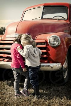 Photo by Ana Carolina Mönnaco - Young girls telling secrets by an old red pickup truck. Best friends.