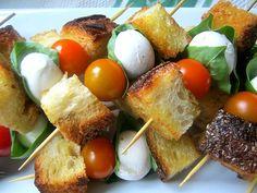 Skewer of rustic bread, mozzarella ball, basil leaf and grape tomoato drizzled in viniagrette