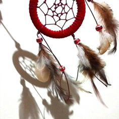 -Filatro dos Sonhos; -Apanhador dos sonhos; - Vermelho; - Penas; - Miçangas estilizadas; - Raio = 8,2cm