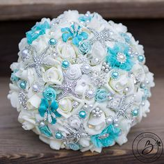 """""""Aqualicious"""" large brooch wedding bouquet with starfish brooches, jewels, pearls and aqua teal accents  Are you having a beach themed wedding on a cruise ship that wont let you bring real seashells on-board? This is the perfect solution! This ornate and beautifully detailed jeweled wedding bouquet is made with our quality Soft Touch roses that are sturdier, better quality, and more realistic than the traditional craft store silk flowers! Only the best flowers make the cut in this sparkly…"""