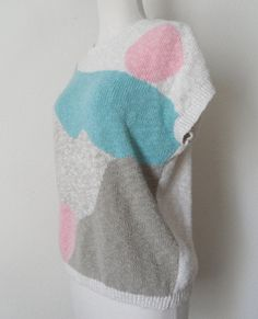 White cap sleeve knit sweater with pastel pink, blue and tan abstract design. Oversized, casual fit with rib knit neckline, sleeve cuffs and hem.