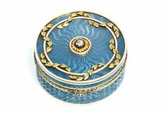 A Jewelled Two-Colour Gold Mounted Guilloché Enamel Pill-Box  Marked Fabergé, with the workmaster's mark of Feodor Afanassiev, St Petersburg, 1908-1917, indistinct scratched inventory number, possibly 18523  Circular, the body enamelled in translucent grey over a wavy guilloché ground within opaque white enamel and bright-cut borders, the hinged cover centering a gold-mounted rose-cut diamond, within a chased gold foliate garland, the laurel chased border with diamond set thumb-piece