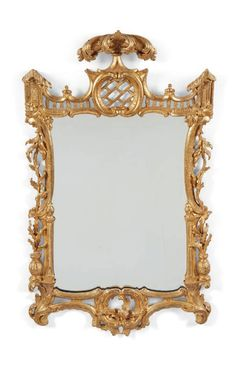 A GEORGE III GITLWOOD MIRROR, CIRCA 1760. The rectangular within a stylised foliate swag-carved frame surmounted by rocaille, latticework and acanthus scrolls, fanked by balustrades and picturesque buildings - Dim: 44 3/4 in. (114 cm.) high; 26 in. (66 cm.) wide.