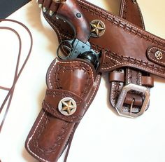 """Gunfighter style Quickdraw"""" holster and belt with BP's Santa Fe style border tooling, Texas Gold Star conchos and Cody Engraved buckle. Hand made to fit by Maker Brett Park at Circle KB Holsters. Cowboy Holsters, Gun Holster, Leather Holster, Cowboy Gear, Western Cowboy, Cowboy Action Shooting, The Lone Ranger, Leather Projects, Leather Working"""