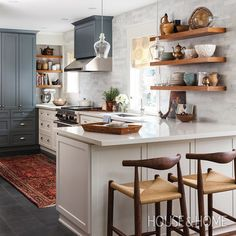 """""""We love this warm kitchen with two-tone cabinets and wood shelving by Qanūk @qanukinteriorsinc [Photo: Donna Griffith]"""""""
