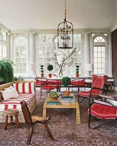 SUNROOM IN TUXEDO PARK    Red-and-white upholstery and an array of topiaries bring color to the grandly scaled sunroom of a Tuxedo Park, New York, home decorated by Ernest de la Torre. A woven-rattan chaise and vintage armchairs surround a Jean-Michel Frank-inspired cocktail table.
