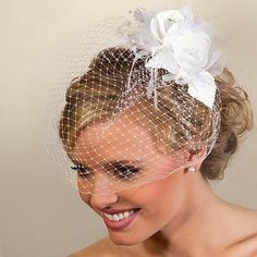 Make a bold statement with this modern double rose cage bridal veil. Bringing that vintage flair to your wedding look, this veil features two silk roses at its top, beautifully overflowing into its white caged netting.