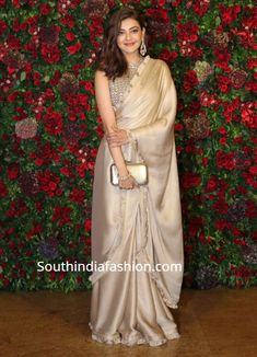 Kajal Aggarwal attended Deepika Padukone and Ranveer Singh's wedding reception wearing a plain gold satin saree that has ruffled borders paired with matching embellished high neck blouse. Kajal aggarwal saree in deepika reception Saree Draping Styles, Saree Styles, Fancy Sarees, Party Wear Sarees, India Fashion, Look Fashion, Fashion Clothes, Indian Dresses, Indian Outfits