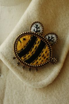 Heres a sweet little bee brooch.  This brooch is made with recycled sweater felt and thrifted brass zipper pieces. This piece has been further