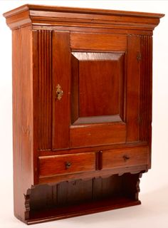 """Conestoga Auctions -  Harry B. Hartman Estate Auction - Session II  May 16, 2015.  Lot 720.      Estimate:$2,500 – $3,500.  Sold: $4,130.   Description:  Pennsylvania Chippendale Walnut Hanging Cupboard. Molded cornice, raised panel door, flanked by reeded stiles, two split lower lip molded dovetailed drawers, lower shelf with scalloped skirt and supports, dovetailed construction. 35-1/2""""h. x 26-3/4""""w. x 10- 1/2""""d. Condition: Very good, expected wear, old refinish."""