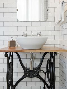 In the other bathroom is a sink on a stand made from an antique Singer sewing…