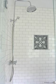 White subway tile is a classic. I love the charcoal gray grout and the patterned tile that looks like cement tile in the shower cubby