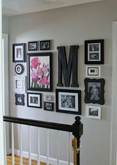 Choose one or two focal points before building your gallery wall. This blogger went with a pop of color and a bold family monogram. Keep the rest of your gallery wall simple and consistent to let the main pieces do the talking.