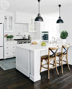 Gorgeous! White cabinets, dark floors, and no brass in sight! The light fixtures aren't my favorite, but at least they aren't chandeliers.