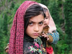 A young girl carries her baby brother as she walks back to her hometown, Taubat, in the Neelum Valley. (Azad Jammu & Kashmir) Photographer: Tapu Javeri