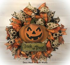 Halloween Wreaths, Halloween Wreath, Pumpkin Wreath, Primitive Halloween Wreath, Farmhouse Wreath, Fall Wreath, Halloween Decor, Halloween, Halloween Decoration, Primitive Wreath, Front Door Wreath, Autumn Decor, Farmhouse Decor.  This cute, jack-o-lantern will welcome trick or treaters of all ages with Halloween charm. Made on a black work wreath frame with burlap fabric, orange burlap ribbon, burlap and moss green polka dot ribbon, Halloween plaid ribbon, burlap and black polka dot ribbon…