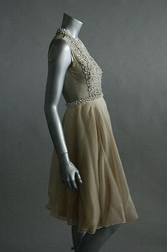 A Madame Grès grey chiffon cocktail gown, late 1950s, labelled and with additional atelier tag `Mme Marguerite, Katia no 8078, the bodice front covered with silver and white bugle beads, studded with rhinestones, transparent back bodice, layered chiffon skirt over silk jersey ground. Sideway