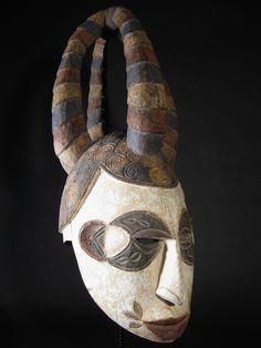 Africa   'Ikorodo' Helmet 'Maiden Spirit' mask from the Igbo people of Nigeria. Wood with pigment. These masks which represent the spirit of a yung firl, would have been worn by young men (in girls clothes) at Harvest ceremonies held in honour of the Earth Spirit. The quadruple twisted coiffure is typical of that worn by the young girls in the region.   ca. post 1940.