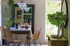 En el comedor diario, mesa de petiribí con tapa de mármol de Carrara y sillas de mimbre. Lámparas colgantes 'Ferroviarias' y espejo con marco negro (todo de Galpón 8).