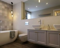 Baño aire retro pero de línea actual. Bañera exenta e inodoro con cisterna oculta. Lavabos de sobre encimera y mueble suspendido. Pavimento porcelánico imitación roble y revestimiento imitación mosaico. Diseño realizado y desarrollado por AZ diseño.