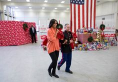 First Lady Michelle Obama is escorted by SSgt Joel Vazquez as she arrives with a sack full of 900 toys at the Toys for Tots Distribution Center at Joint Base Anacostia-Bolling in Washington, D.C., Dec. 11, 2012. (Official White House Photo by Lawrence Jackson)