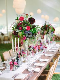Rustic wedding table with marquee and paper lanterns with benches and bright coloured floral displays