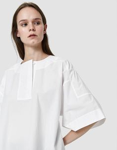 Popover top from Acne Studios in White. Round neckline. Concealed, wide quarter-button placket. Dropped shoulders. Short sleeves. Straight hem. Boxy silhouette. • Poplin • 100% cotton • Dry clean #acnechest