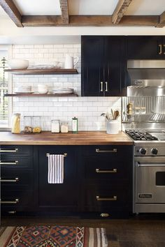 Black cabinets, open wood shelving, wood beams