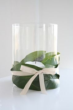Magnolia leaves wrapped around glass...add a floating magnolia flower or candle and this would be gorgeous!!