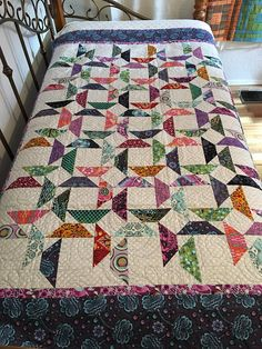 This is a modern inspired quilt featuring fun fabrics from Tula Pink. They layout of the colored pieces against the neutral background creates a field of stars. Fabrics are in a variety of colors including pink, green, blue, purple, red, and more. Background fabric is white with a