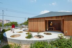 'house in mukainada' is a single family dwelling set on a circular planted pathway that incorporates designated areas for natural vegetation.