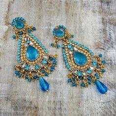Erumi - Gold earrings made to dazzle the night away with gold and blue stone accents. Sitting delicately on your lobes, swaying gently and sparkle fiercely.