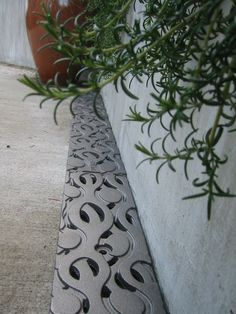 Could have similar inset stainless steel coverings along the perimeter of the garden wall.  www.drainagekits.com