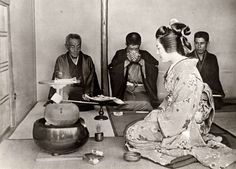Wedding ceremony in Japan, 1922. The bride offer a cup of tea to her future husband, who sits in between two groomsmen.