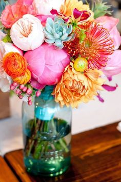 Bright sherbert colored flowers in blue mason jar for centerpiece - keeps a more casual feel