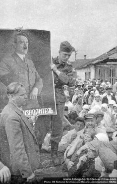 German propaganda troops distribute Adolf Hitler posters to Ukrainian villagers, summer 1941. In the foreground, a Ukrainian collaborator makes a presentation in the native language. Many Ukrainians welcomed Nazi troops as liberators after fourteen years of Soviet rule.