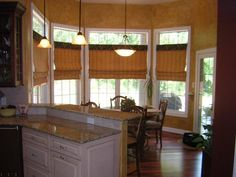 We designed these flat roman shades for this awesome dinette setting...and for a touch of blending them with the rest of the kitchen...we did a contrasting valance/cornice...they are stunning!