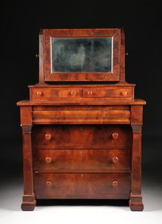 "AN AMERICAN EMPIRE FLAME MAHOGANY DRESSER, 19TH CENTURY, the framed swivel mirror supported by obelisks on two inset short drawers, flanked by rectangular columns, on cushion molded square feet. Height: 67 1/2"" Width: 45 3/8"" Depth: 21 3/8"""