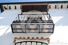 Photo made in Grazalema-El Bosque-Benaojan Andalusia (Spain). The picture shows some details of the white facade of a typical house in the country. You see a balcony whose bottom is decorated with tiles and railing and wrought iron railing.