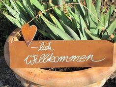 """Edelrost Schild mit Herz """"Herzlich Willkommen""""  Wunderschönes Edelrost Schild mit einem Herz als Dekoration für Haus und Garten.  Auch als Geschenk für gute Freunde und Bekannte eine tolle Idee.  Das Schild ist zum Hängen und wird inkl. Bastband geliefert.  Das Edelrost Schild ist mit folgendem Spruch versehen:  """"-lich Willkommen.""""  Größe:      Höhe: 16 cm     Breite: 35 cm  Preis: 13,- €"""