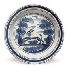 AN ENGLISH DELFT BLUE AND WHITE PLATE CIRCA 1710-1725, PROBABLY LONDON Painted with a lion among sponged trees, within concentric bands