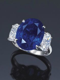 A SAPPHIRE AND DIAMOND RING, BY HARRY WINSTON Set ~ with a cushion-shaped sapphire weighing approximately 14.49 carats,