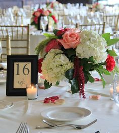 Julep silver bowls filled with white hydrangea, coral, fushia and pink roses, carnations, burgundy and green hanging ameranthus and salal greens.
