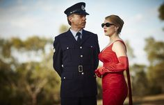 """Kate Winslet as Myrtle """"Tilly"""" Dunnage wearing her red Italian silk dress at a football game alongside Hugo Weaving as Sergeant Horatio Farrat. Costume design by Margot Wilson and Marion Boyce respectively. Movie Costumes, Cool Costumes, The Dressmaker Movie, Hugo Weaving, Hollywood Costume, Beautiful Costumes, Kate Winslet, Mode Vintage, Vintage Style"""