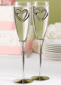 """The love of two hearts linked together is a lasting image of your wedding day. These sparkling toasting flutes are set on nickel-plated stems with a band of petite hearts at the base of each glass bowl. Gleaming rhinestone-studded, linked hearts decorate the front of each glass. Add two lines of your personalization to be engraved on each glass as a heart-felt memento of your wedding day.  Features and Facts:   Flutes are 10 1/4"""" tall  Silver-plated metal base with glass bowl…"""