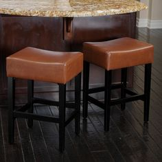 Modern elegance meets contemporary design in these backless leather counter stools. This pair of two stools features hardwood construction with a soft, comfortable bonded leather seat in a neutral color that will blend in with any decor setting.