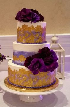 A black and white striped topper cake with purple fondant flowers ...