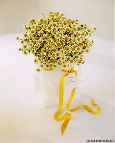 A little goes a long way with this table decoration. Fresh German chamomile is placed in a jar, then enclosed in a white paper bag for an exuberant centerpiece that is also economical. The top of the bag is trimmed with scalloping scissors, folded, punched with holes, and laced with yellow ribbon. Thread a tag with the table number onto ribbon before tying.