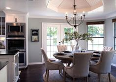 In this classically chic dining room, the light blue walls and white ceiling offer a perfect contrast to the dark furniture and chandelier. | Pulte Homes